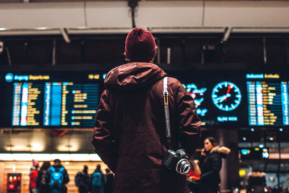 Person looking at departure board deciding where to travel to next